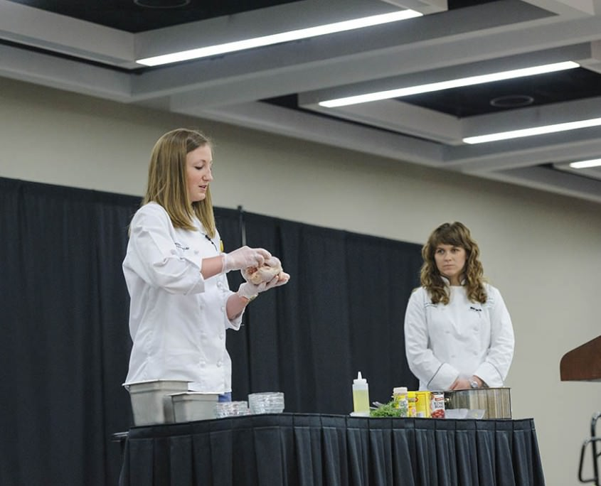 Chef Leah Sarris (right), program director of the Goldring Center for Culinary Medicine at Tulane University School of Medicine in New Orleans, and culinary nutrition intern Christine Blank demonstrate how to prepare a chicken for roasting at the 16th annual Rural Health Conference.